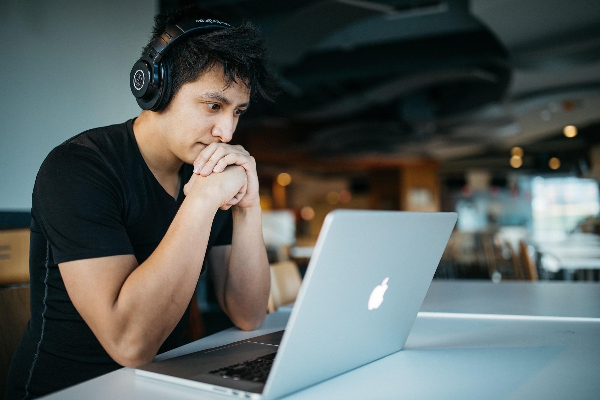 Junger Mann sitzt vor einem Laptop